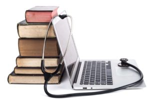 books as a stand for a laptop with stethoscope