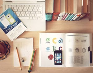 books, phone, laptop, paper and pencils on the table