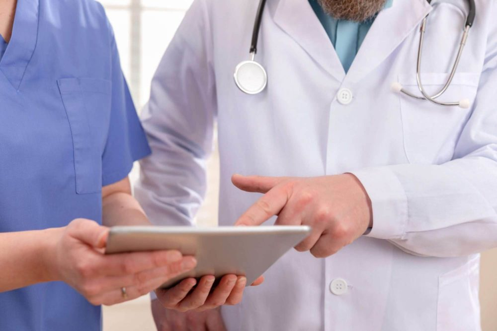 Doctor and nurse discussing patients tests at tablet computer in a hospital