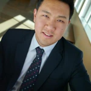 Dr. Michael Chiu wearing a black suit with a dotted tie